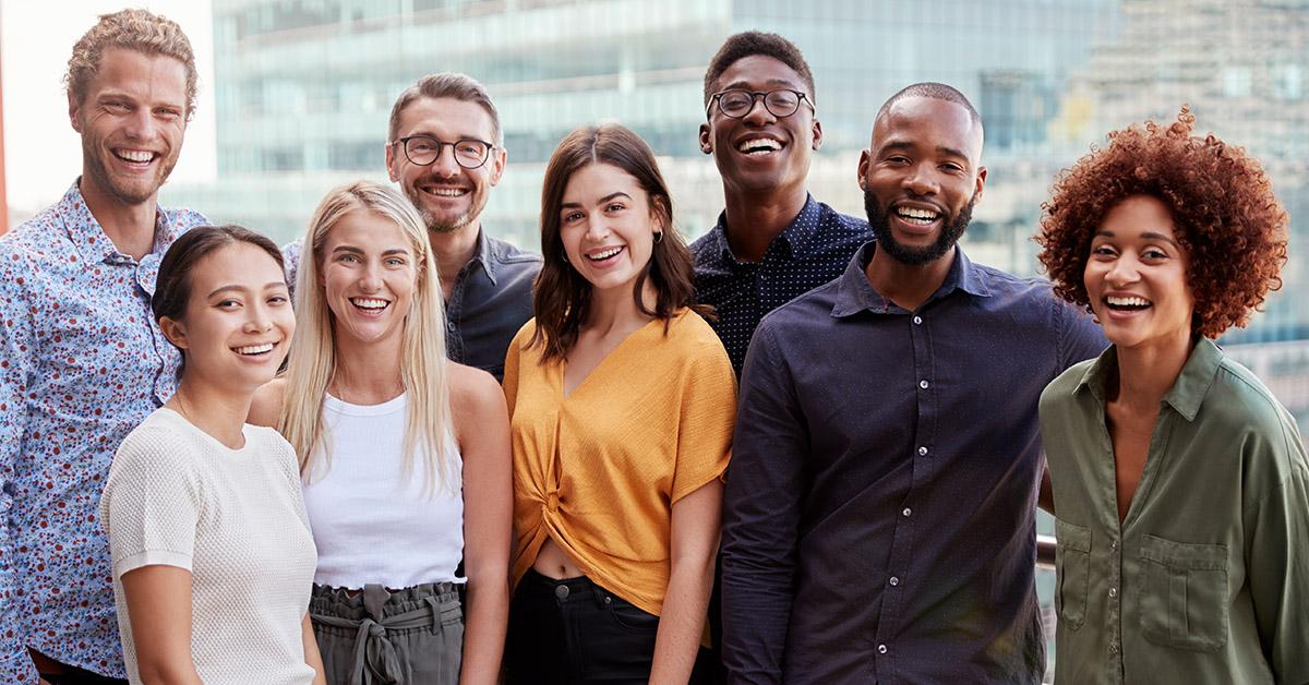 Várias pessoas sorrindo em um ambiente corporativo