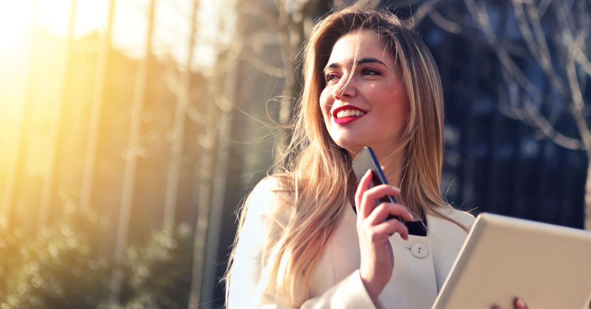 Uma mulher sorrindo com o celular na mão