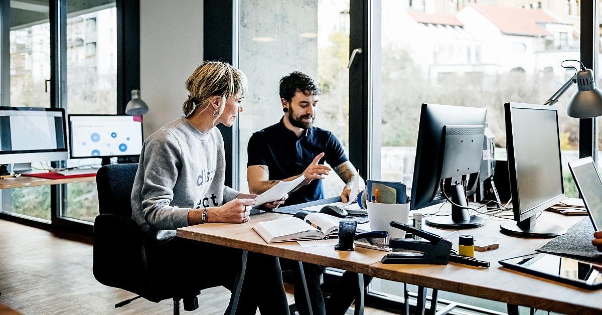 duas pessoas olhando para a tela de um computador em um ambiente corporativo