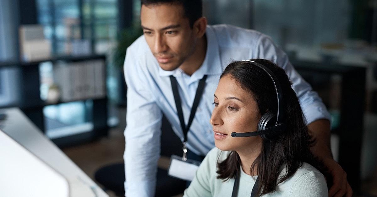 a imagem mostra uma profissional de contact center durante um atendimento e um colega de trabalho ao seu lado observando.